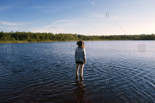 Woman with a hat standing in a lake