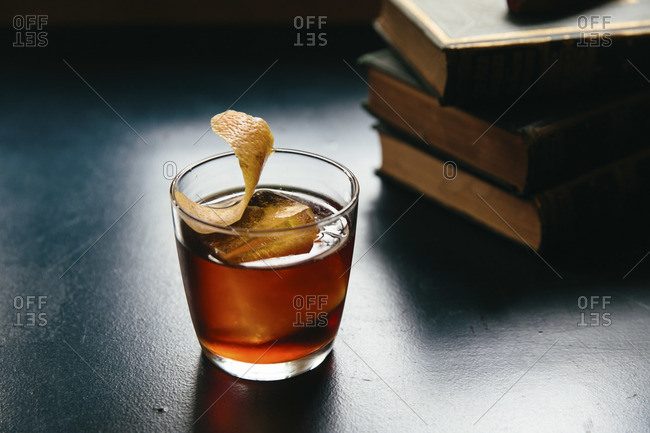 Old fashioned cocktail with an orange twist served on a table