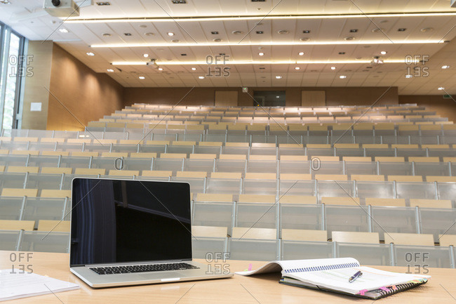Laptop and notebooks on lectern at an auditorium