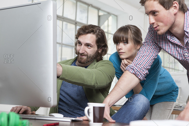 Three colleagues looking at computer in a creative office