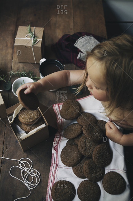 Overhead view of young girl putting gingersnap cookies into paper box
