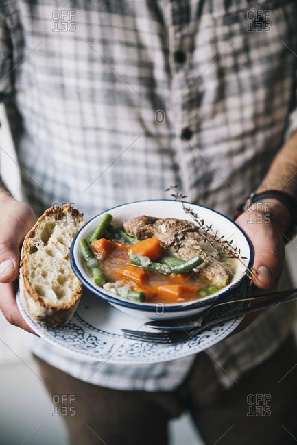 Man holding a bowl of spring lamb stew