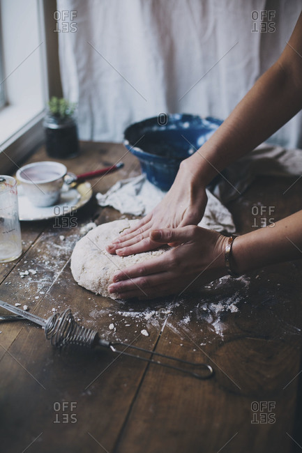 Woman gently forming dough on a lightly floured surface