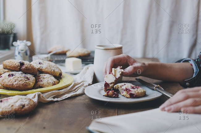 Woman eating cranberry scone with butter