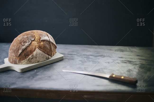 Half loaf of rustic bread on a cutting board