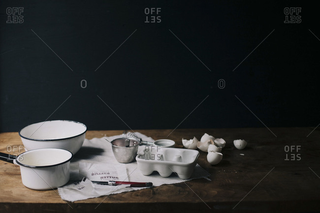 Pans and cracked eggshells on a table