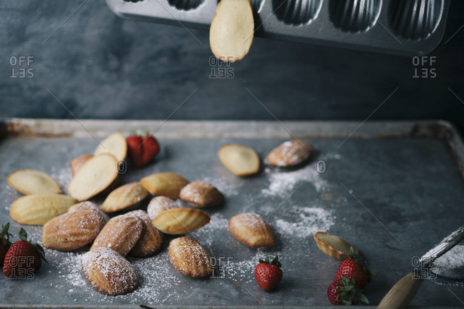 Freshly baked madeleines falling out of a pan