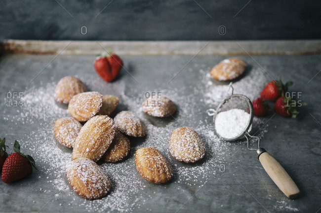 Fresh madeleines with strawberries and icing sugar