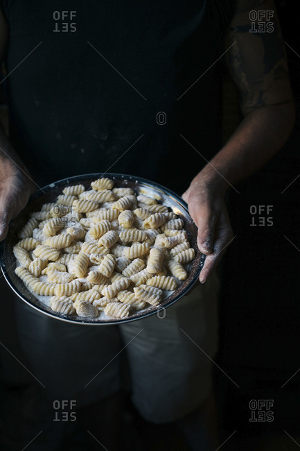 Man holding a plate of raw gnocchi