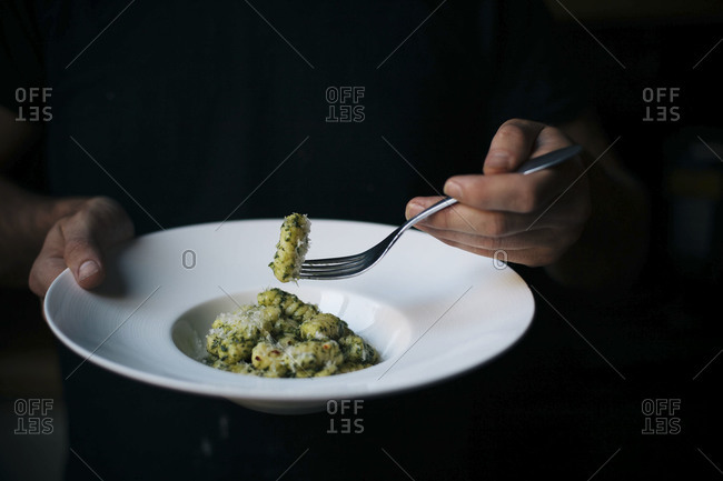 Man eating gnocchi with salsa verde