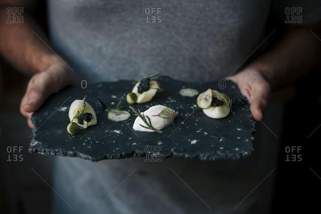 Man holding a caviar platter