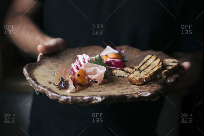 Man serving a charcuterie board