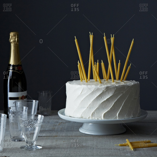 Beeswax candles on a cake served with champagne