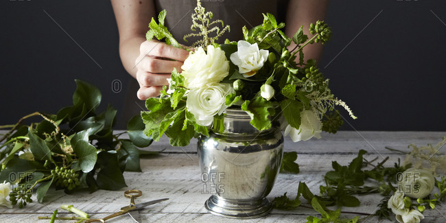 Woman arranging flowers in a pewter vase