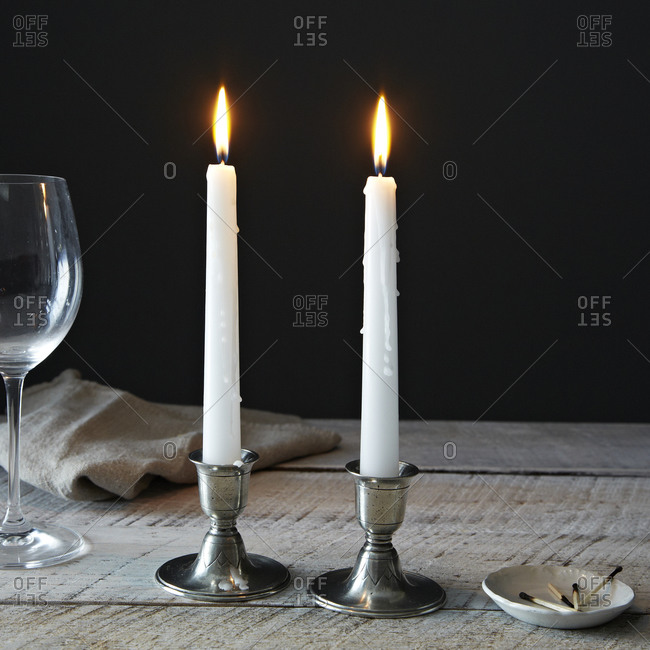 Two white candles in pewter candlesticks