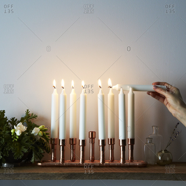 Close up of woman lighting a copper menorah