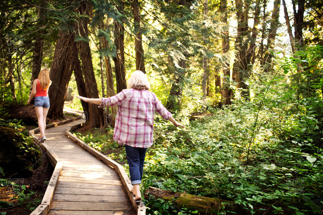Mother and adult daughter balancing on wooden pathway in forest