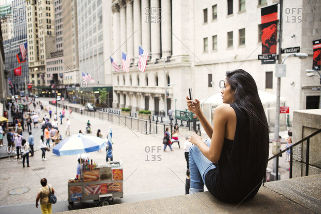 New York City - June 8, 2014: Woman checking smartphone on steps of Federal Hall near the New York Stock Exchange