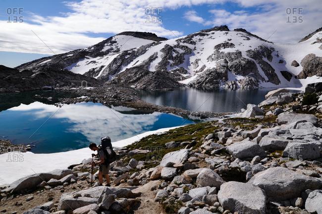 Man hiking at a tarn in the Enchantments mountain range, Washington