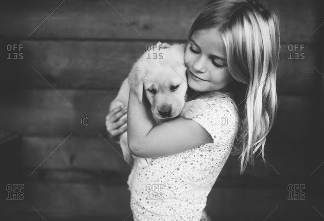 Young girl hugging a puppy