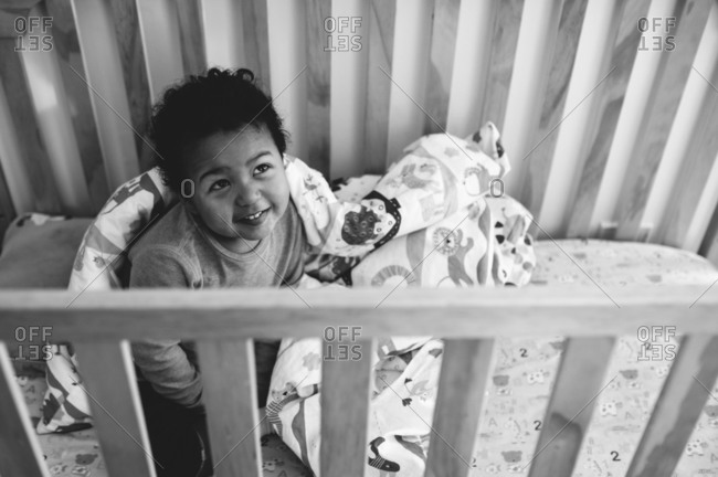 Smiling baby sitting in crib