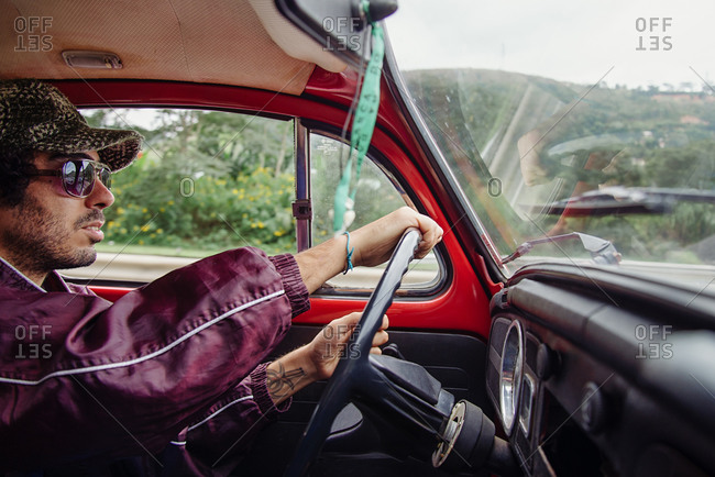 Rio de Janeiro, Brazil - June 4, 2014: Young man driving a car in the countryside