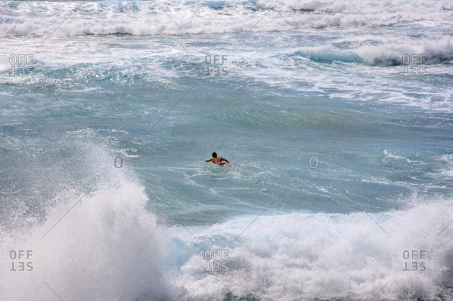 Man swimming in the ocean amidst large waves