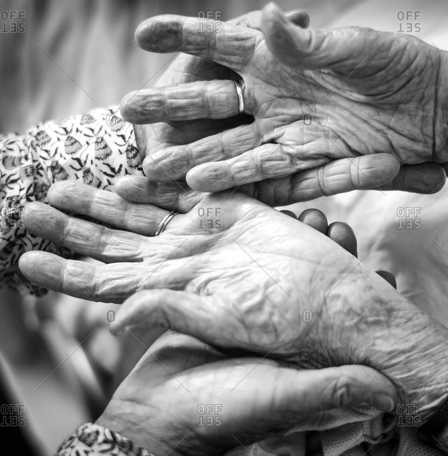 Close up of a person holding the hands of an elderly woman