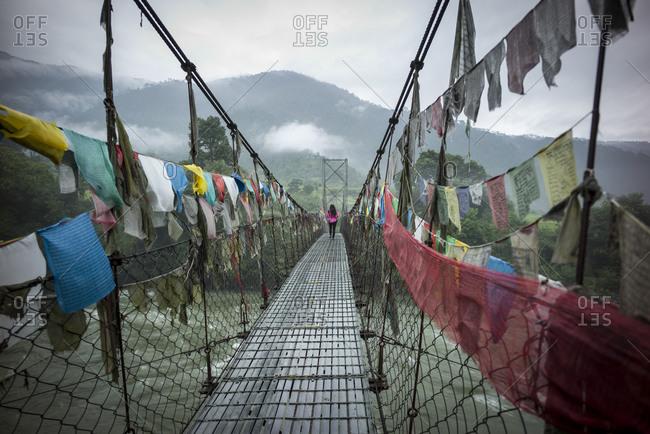 Woman crossing a suspension bridge covered in prayer flags, Bhutan