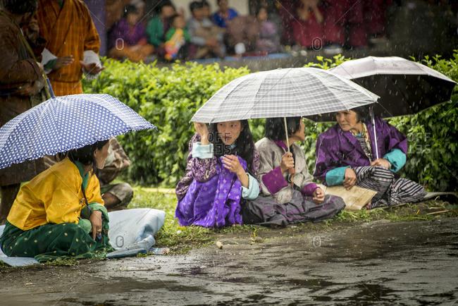 Bumthang, Bhutan, South Asia - September 15, 2013: Women sitting under umbrellas in Bumthang, Bhutan