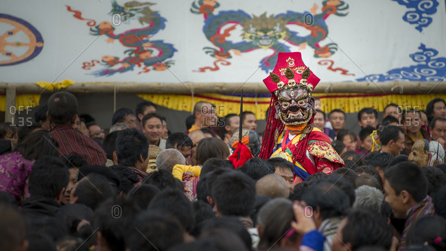 Bumthang, Bhutan, South Asia - September 16, 2013: Crowd on a Religious festival in Bhutan with a dancer in traditional mask