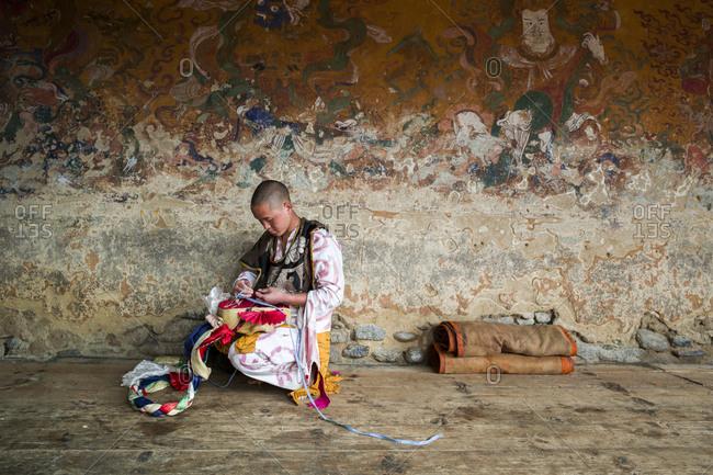 Bumthang, Bhutan, South Asia - September 16, 2013: Young man tying a mask at a wall in Bumthang, Bhutan