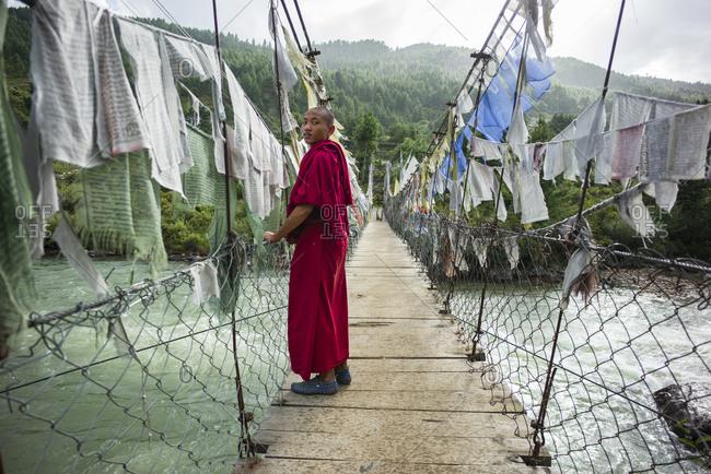 Bumthang, Bhutan, South Asia - September 17, 2013: Monk standing on a suspension bridge in rural Bhutan