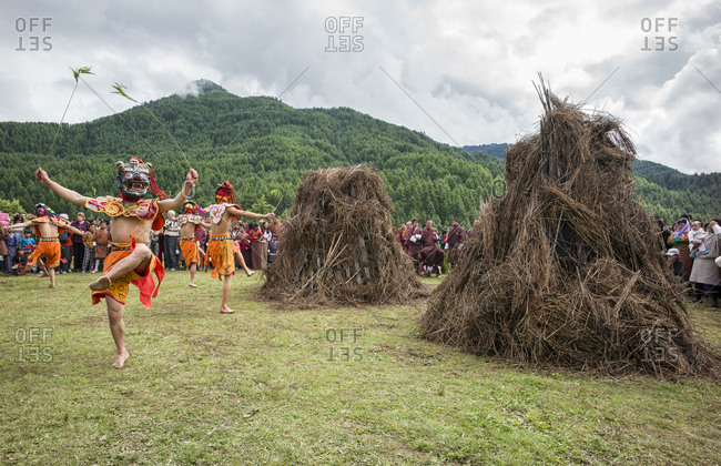 Bumthang, Bhutan, South Asia - September 19, 2013: Masked dancers at the Thangbi Mani fire festival in Bhutan