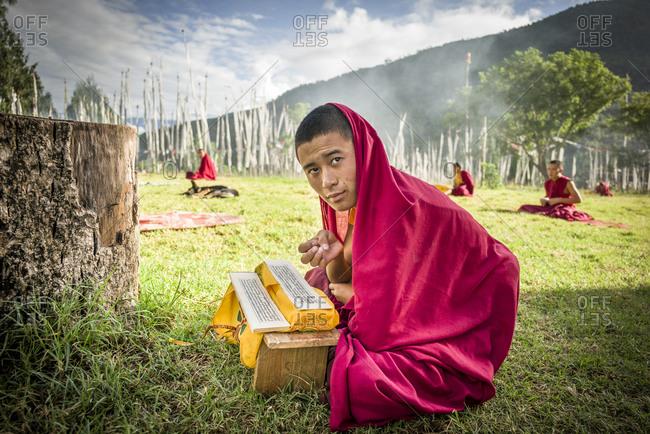 Bumthang, Bhutan, South Asia - September 19, 2013: Monk praying at Lobesa Monastery in Bhutan