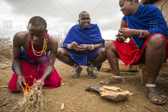 Maasai lands, Tanzania - October 2, 2013 - Maasai men show their skills at lighting a fire