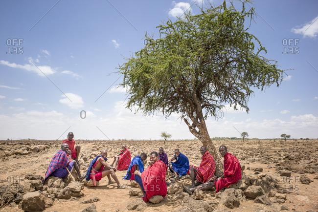 Maasai lands, Tanzania - October 2, 2013 - Maasai men of the village sit and talk under the tree of knowledge