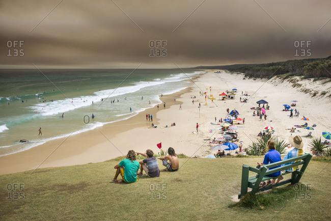 Holiday makers watch the beach goers as bushfire smoke hovers over North Stradbroke Island