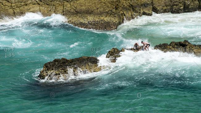 North Stradbroke Island - February 19, 2014: Dangerous clambering on rocks amidst the waves, North Stradbroke Island