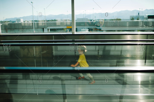 View of young girl running on moving sidewalk