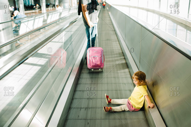 Young girl traveling by moving sidewalk