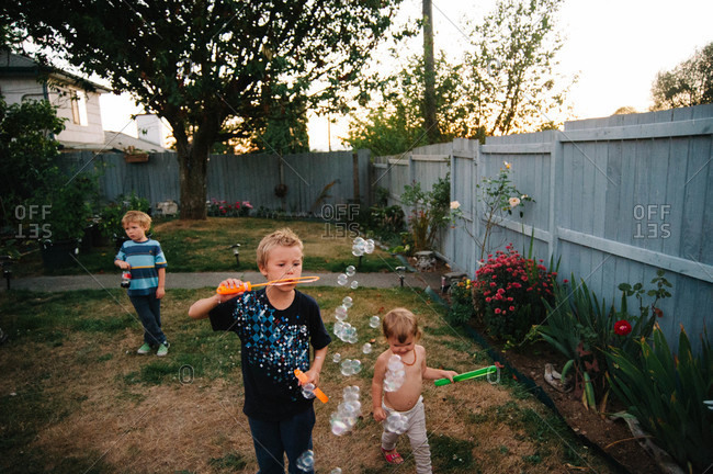 Children blowing soap bubbles at the backyard