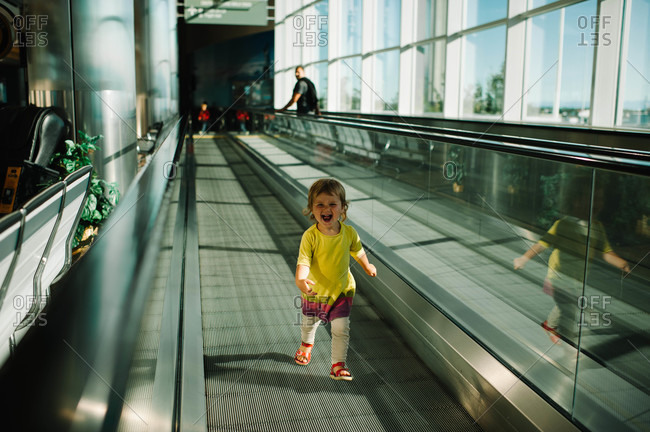 Cheerful girl on moving sidewalk