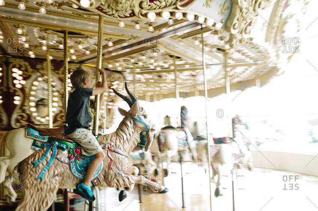 Boy riding on a carousel