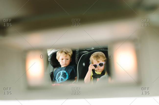 View in the rear-mirror children traveling by car