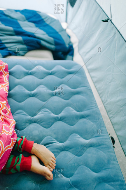 Low section view of kid sleeping on inflatable mattress