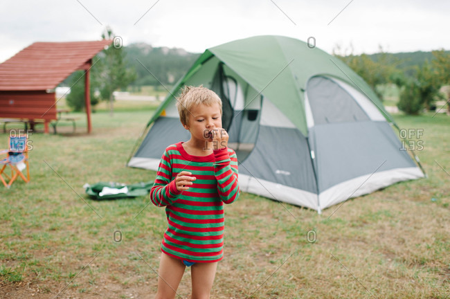 Young boy eating outside at a tent
