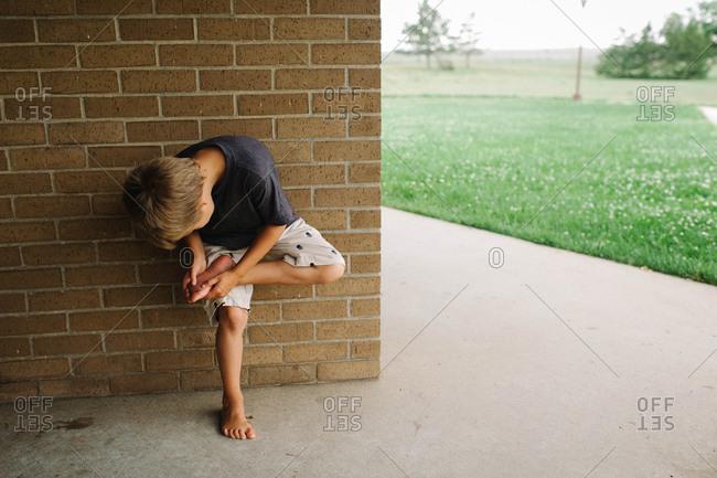 Boy checking his foot at a wall