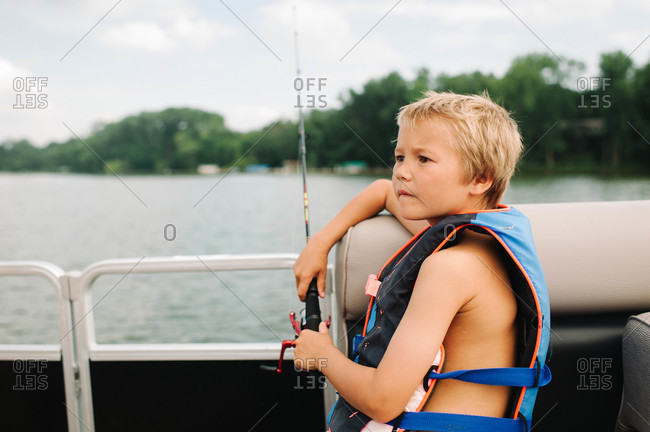 Young boy in a life fest fishing on a boat