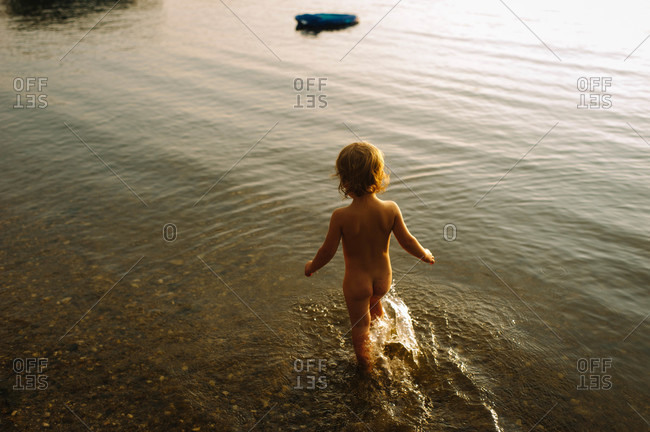 Back view of naked toddler walking in shallow water